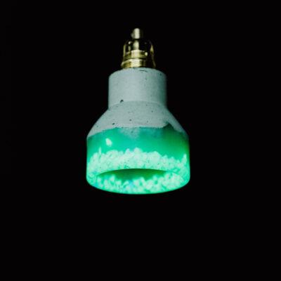 Lampa z betonu i żywicy w kolorze morskiej zieleni. Specjalne kruszywo świeci nawet, gdy nie jest włączone. Lampa betonowa ozdobiona podsufitką w kolorze złotym.