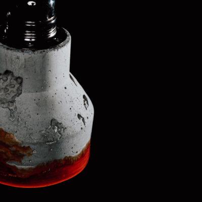 Lampa z betonu architektonicznego z elementem żywicy i podsufitką w kolorze czarnym. Lampa betonowa ma okrągły kształt, u dołu jest zakończona żywicą w kolorze czerwono-pomarańczowym.