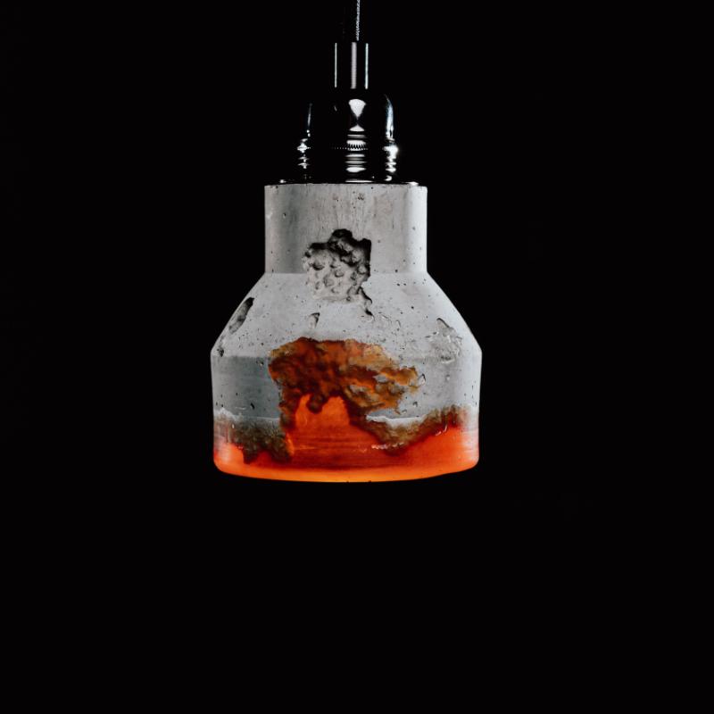 Lampa z betonu architektonicznego i z elementami żywicy dekoracyjnej. Na górze lampy betonowej umieszczono podsufitkę w kolorze czarnym. U dołu element z żywicy w kolorze czerwono-pomarańczowym.