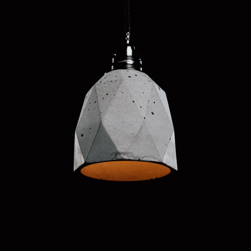 Lampa z betonu w stylu loftowym. Ma charakterystyczny heksagonalny kształt i wyraźne ślady ręcznego wykonania: pęcherze powietrza, nierówności i zacieki. Lampę betonową wieńczy czarna podsufitka i czarny, prosty przewód.