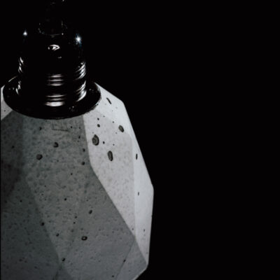 Lampa z betonu lofotwa. Ma heksagonalny kształt i jest ozdobiona czarną podsufitką. Lampę betonową zdobią ślady ręcznego wykonania: pęcherze powietrza i nierówności.