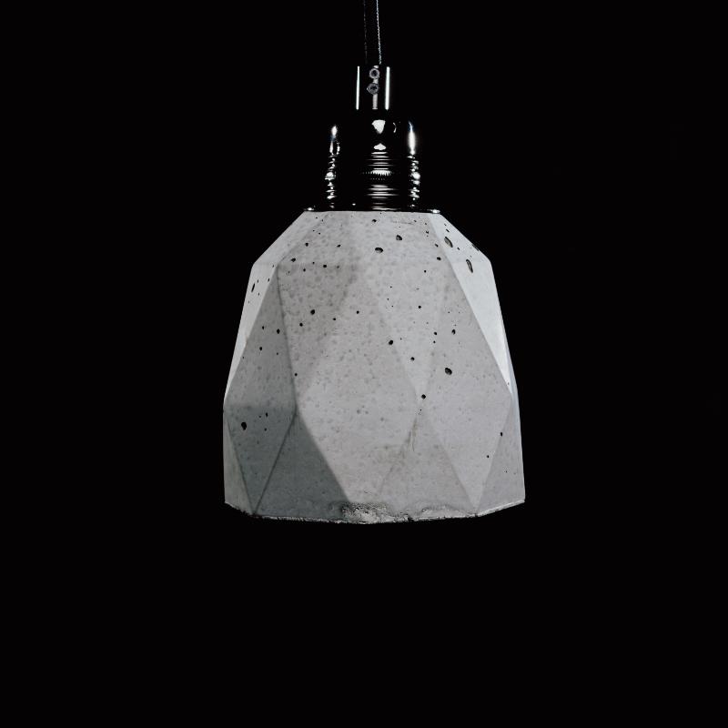 Lampa z betonu, loftowa o charakterystycznym heksagonalnym kształcie. U góry ozdobiona czarna podsufitką i prostym, czarnym przewodem. Ślady ręcznego wykonania lampy betonowej: pęcherze powietrze, zacieki dodają jej niepowtarzalnego charakteru.