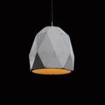 Lampa z betonu minimalistyczna o heksagonalnym kształcie, z prostym czarnym przewodem. Lampa betonowa ma charakterystyczne ślady ręcznego wykonania.