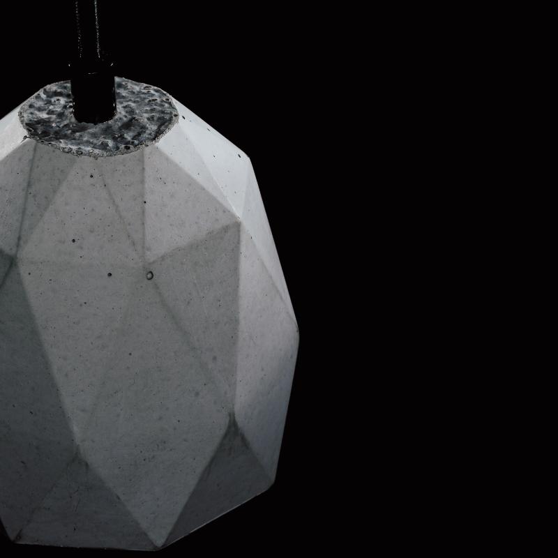 Lampa z betonu dekoracyjnego, minimalistyczna. Ma heksagonalny kształt i charakterystyczne ślady ręcznego odlewu: pęcherze powietrza i niejednolitą strukturę. Lampa betonowa jest montowana na prostym, czarnym przewodzie.