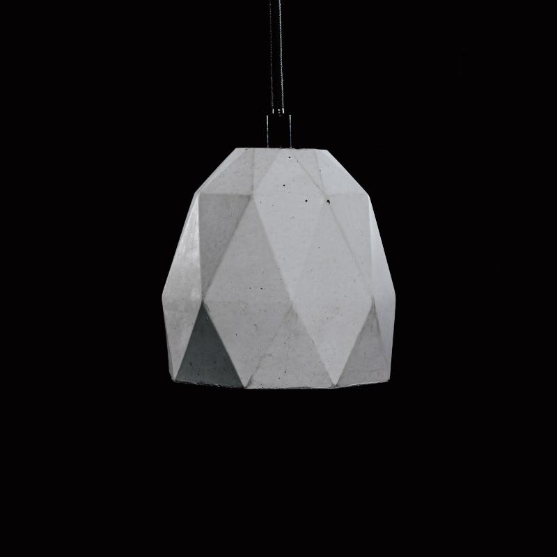 Lampa z betonu dekoracyjnego, minimalistyczna. Lampa betonowa ma kształt heksagonalny i jest mocowana na czarnym, prostym przewodzie.