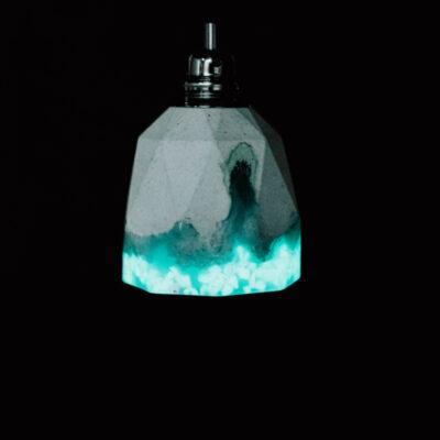 Lampa z betonu dekoracyjnego w kształcie heksagonalnym z ozdobnym elementem z żywicy w kolorze turkusowym i specjalnym kruszywem. U góry lama betonowa zakończona jest podsufitką w kolorze czarnym.