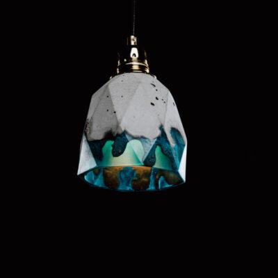 Lampa z betonu dekoracyjnego i żywicy w kolorze lazurowym. Lampa betonowa ma heksagonalny kształt, widoczne ślady różnego odlewu i złotą podsufitkę.