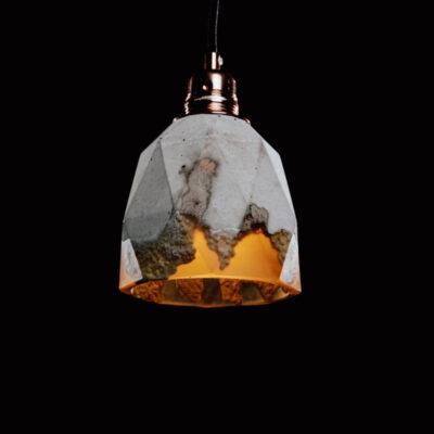 Lampa z betonu dekoracyjnego, rustykalna. Lampa ma kształt heksagonalny, zdobią ją charakterystyczne ślady ręcznego odlewu betonu i podsufitka w kolorze miedzianym.